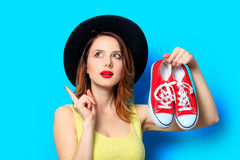 Woman with red gumshoes. Portrait of young surprised red-haired white european woman in hat with gumshoes on blue background Stock Image