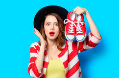 Woman with red gumshoes. Portrait of young surprised red-haired white european woman in hat and red striped shirt with red gumshoes on blue background Stock Photography