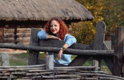Woman with red hair attentively looks into the camera and stands behind a wooden fence in the park royalty free stock image