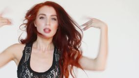 Woman with red hair dances in white studio stock footage