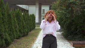 A woman with red hair is dancing in the park. She laughs and rejoices, she is in a good mood. Slow motion stock video