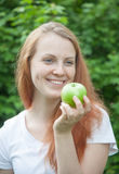 Woman with red hair eats an apple in a park Royalty Free Stock Image