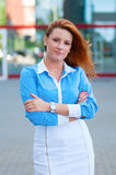 Woman with red hair in front of office building. Royalty Free Stock Photo