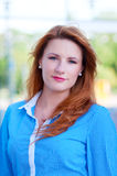 Woman with red hair in front of office building. Royalty Free Stock Photos