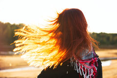 Woman with red hair have fun on the cost in sunlight Royalty Free Stock Image
