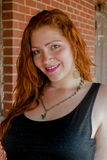 Woman with red hair. Head and shoulders of a young woman with red hair wearing a black sleeveless shirt Stock Images
