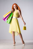 Woman with red hair holding shopping bags Royalty Free Stock Image