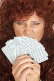Woman red hair look over fan of cards mad Stock Photo