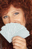 Woman red hair look over fan of cards smile Stock Photos
