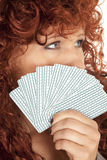 Woman red hair look over fan of cards to the side Royalty Free Stock Photography