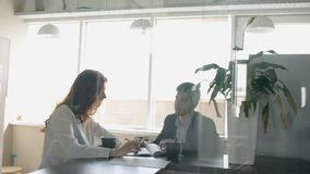 Woman with red hair and man in suit discussing project, sitting at the table. Drinking coffee and taking notes in the office with glass walls. Indoors stock video
