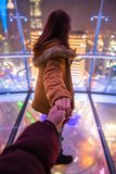 Woman holding man by hand going to night view of city in shanghai. Woman red hair in orange jacket and holding man by hand going to night view of city in royalty free stock photos