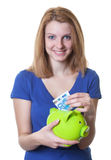Woman with red hair and piggy bank saving money Royalty Free Stock Photo