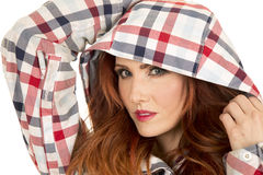 Woman with red hair in plaid hood close hands up royalty free stock photography
