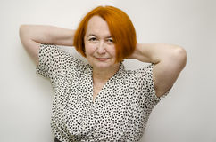Woman with red hair. Redheaded mature woman with hands after a head royalty free stock photo