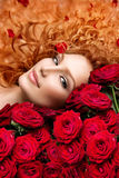 Woman with red hair and roses. Woman with permed red hair and beautiful red roses Royalty Free Stock Photo