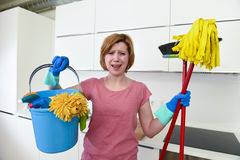 Woman with red hair in rubber washing gloves holding cleaning bucket mop and broom Royalty Free Stock Photos