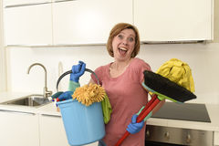 Woman with red hair in rubber washing gloves holding cleaning bucket mop and broom Stock Photo