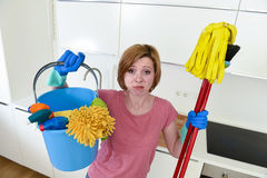 Woman with red hair in rubber washing gloves holding cleaning bucket mop and broom Royalty Free Stock Images