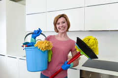 Woman with red hair in rubber washing gloves holding cleaning bucket mop and broom Royalty Free Stock Photography
