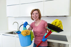 Woman with red hair in rubber washing gloves holding cleaning bucket mop and broom Stock Photography