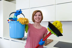 Woman with red hair in rubber washing gloves holding cleaning bucket mop and broom Stock Photos