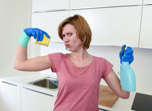 Woman with red hair in rubber washing gloves holding cleaning spray bottle and scourer. Young attractive and happy woman with red hair in rubber washing gloves Royalty Free Stock Photos