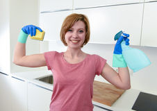 Woman with red hair in rubber washing gloves holding cleaning spray bottle and scourer. Young attractive and happy woman with red hair in rubber washing gloves Royalty Free Stock Photography