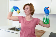 Woman with red hair in rubber washing gloves holding cleaning spray bottle and scourer. Young attractive and happy woman with red hair in rubber washing gloves Royalty Free Stock Image