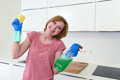 Woman with red hair in rubber washing gloves holding cleaning spray bottle and scourer. Young attractive and happy woman with red hair in rubber washing gloves Stock Photography
