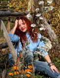 A woman with red hair sits on green grass and looks into the camera. royalty free stock images