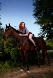 Woman with red hair sitting on a horse Royalty Free Stock Image