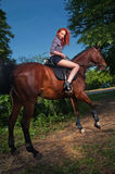Woman with red hair sitting on a horse Royalty Free Stock Images