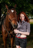 Woman with red hair sitting on a horse Stock Images