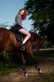 Woman with red hair sitting on a horse Stock Photography