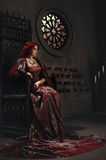 Woman with red hair sitting on a throne stock photos