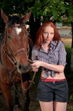 Woman with red hair standing next to horse Stock Photo