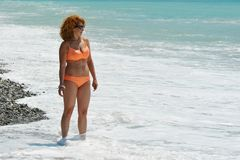 Woman with red hair in sunglasses and an orange swimsuit Stock Image