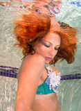 Woman with red hair in a swimming pool. Royalty Free Stock Image