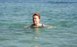 Woman with red hair swims in the ocean Royalty Free Stock Images