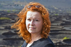 Woman with red hair in volcanic landscape Royalty Free Stock Photography