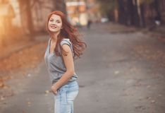 Woman with red hair. Walking by the street Royalty Free Stock Images