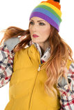 Woman with red hair in yellow vest and hat hands in hair Stock Image
