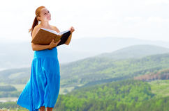 Red haired woman with book on the hilltop Stock Images