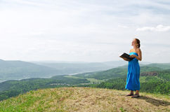 Red haired woman with book on the hilltop Royalty Free Stock Image