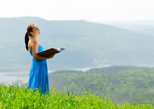 Red haired woman with book on the hilltop Stock Photo