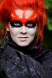 Woman with red hairs and black make-up mask Stock Images