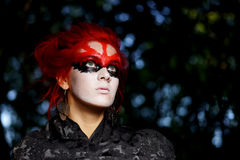 Woman with red hairs and black make-up mask Stock Photo