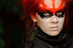 Woman with red hairs and black make-up mask Royalty Free Stock Image