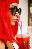Woman with red hairs drink red cocktail. Stock Images